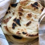 A close up of two pita bread on the left and on the right Four pita bread wrapped in a withe tea towel with blue stripes.