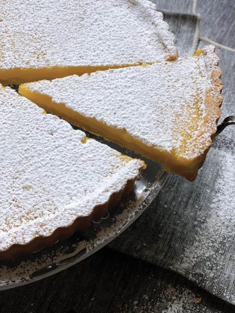 A lemon ginger tart sprinkled with icing sugar with a single piece cut out, ready to serve on a great tablecloth.