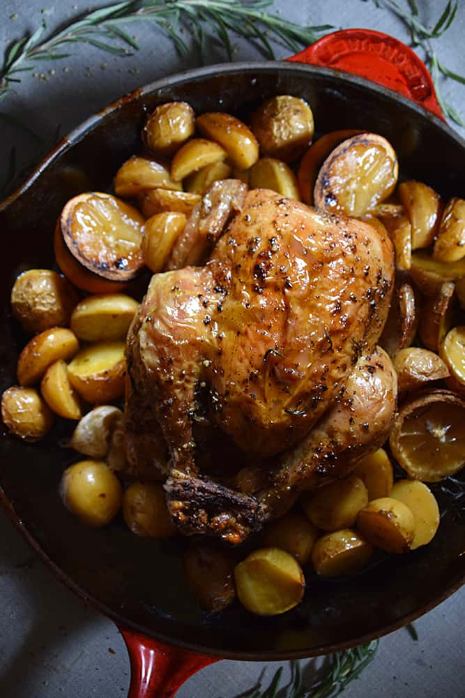 A roasted chicken with potatoes and lemon slices in a cast iron pan.