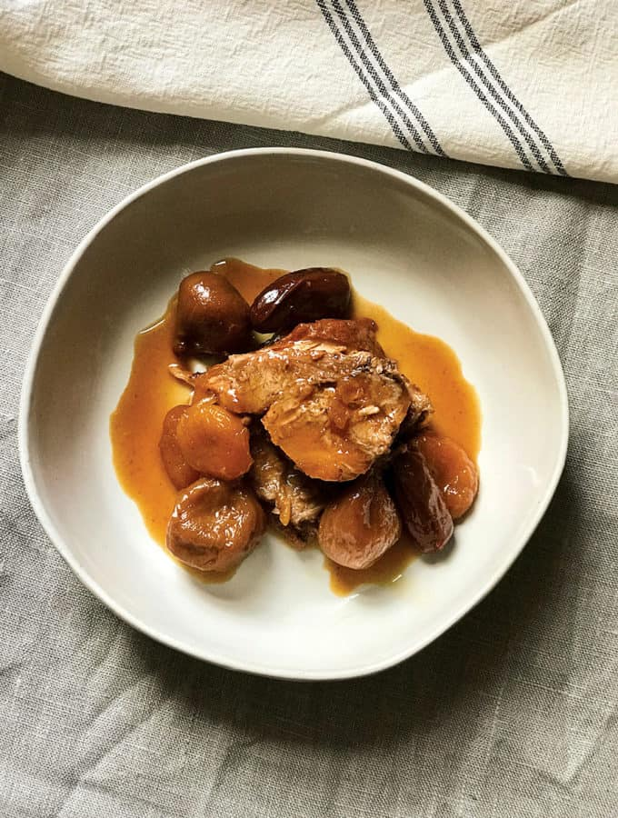 A plate with pork loin roast with figs and apricots.