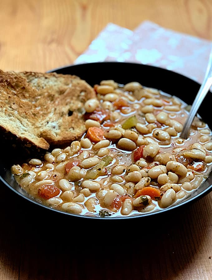 A bowl of white bean soup with carrots and celery, a piece of bread in the bowl and a spoon and a red white flowers napkin.
