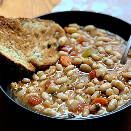 A bowl of traditional Greek white bean soup with carrots and celery, a pieces of bread in the bowl and a spoon and a red and white flowers napkin.