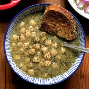 A bowl with Greek chickpea soup and a piece of bread.