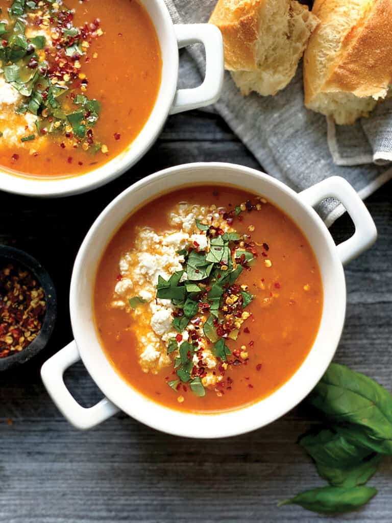 Two bowls of Greek style tomato soup with feta and basil and crusty bread on the side.