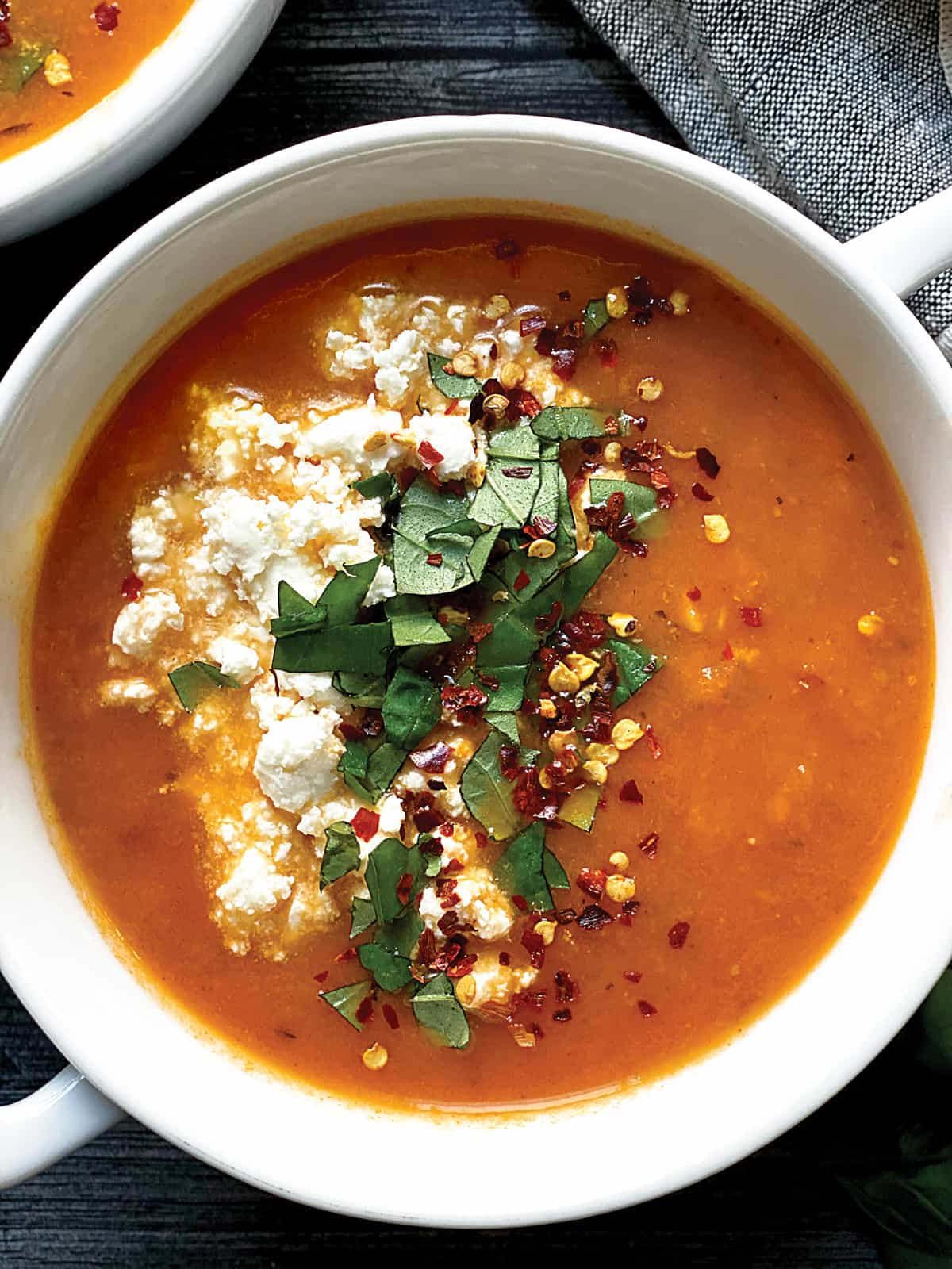 Bowl with tomato soup with basil and feta cheese.