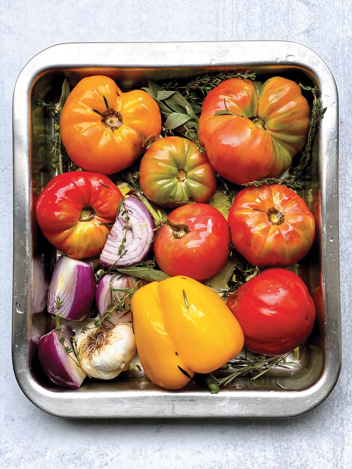 Tomatoes, onions, garlic and bell pepper in a baking dish with fresh herbs.