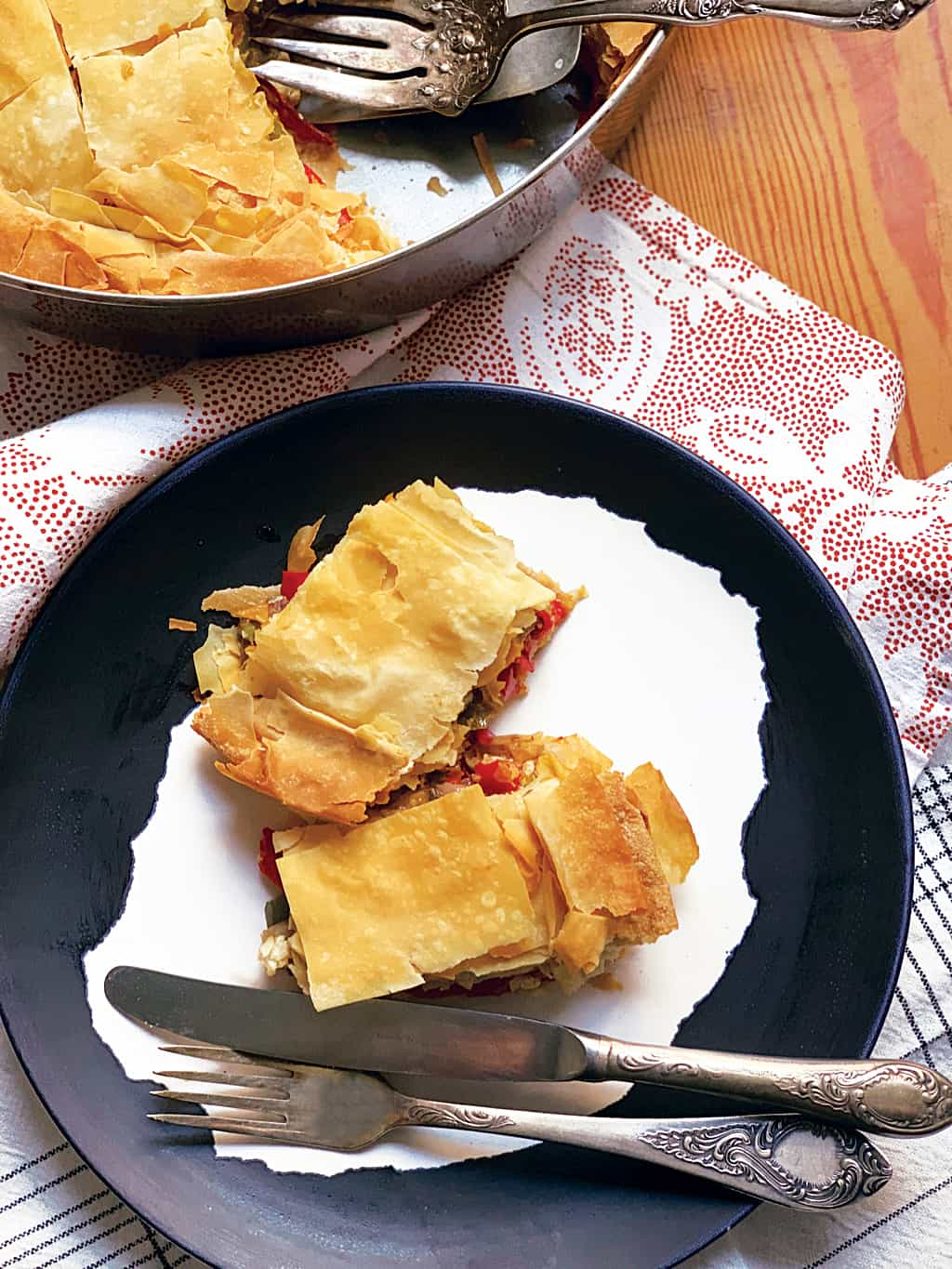 A plate with two pieces of belle pepper pie and utensils.