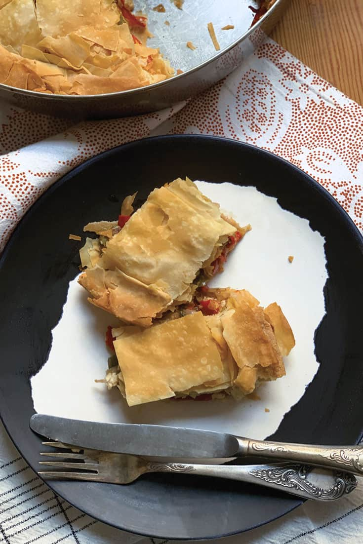 This colorful Greek bell pepper pie recipe is sweet and savory. Made with phyllo, feta and extra virgin olive oil makes a delicious light summer lunch.