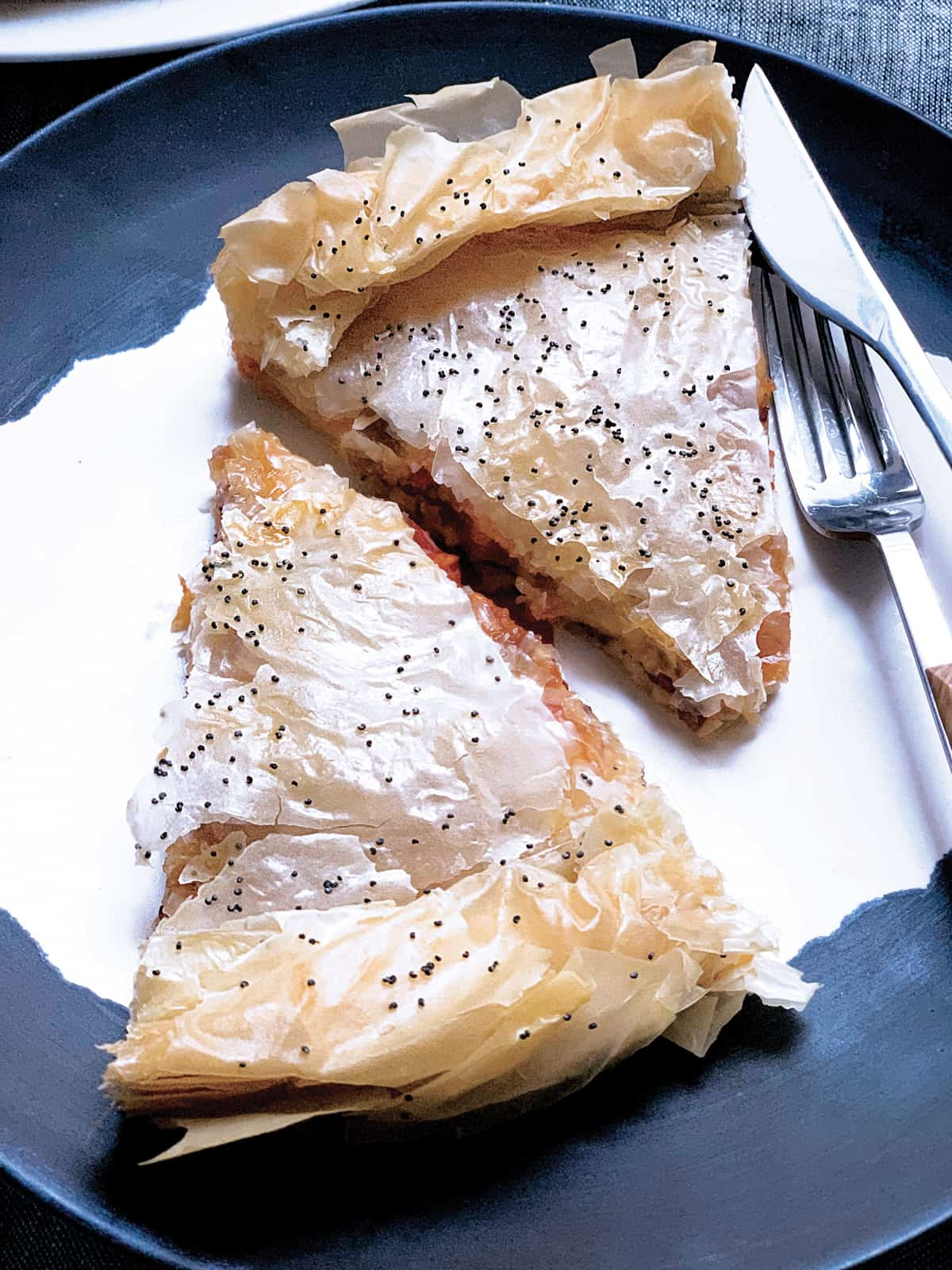 Two pieces of Pastourmadopita pie o a plate with a fork and knife.