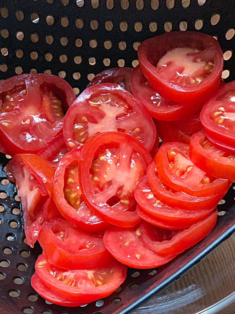 A black strainer with tomato slices.