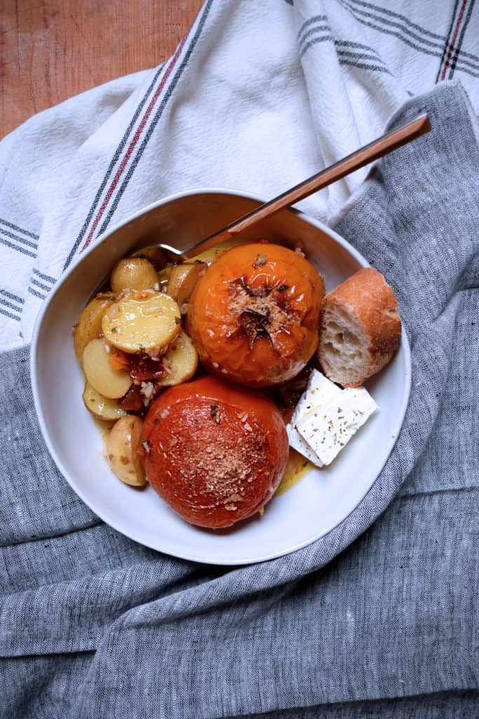 A plate with gemista - stuffed tomatoes and peppers, feta cheese and a piece of bread.