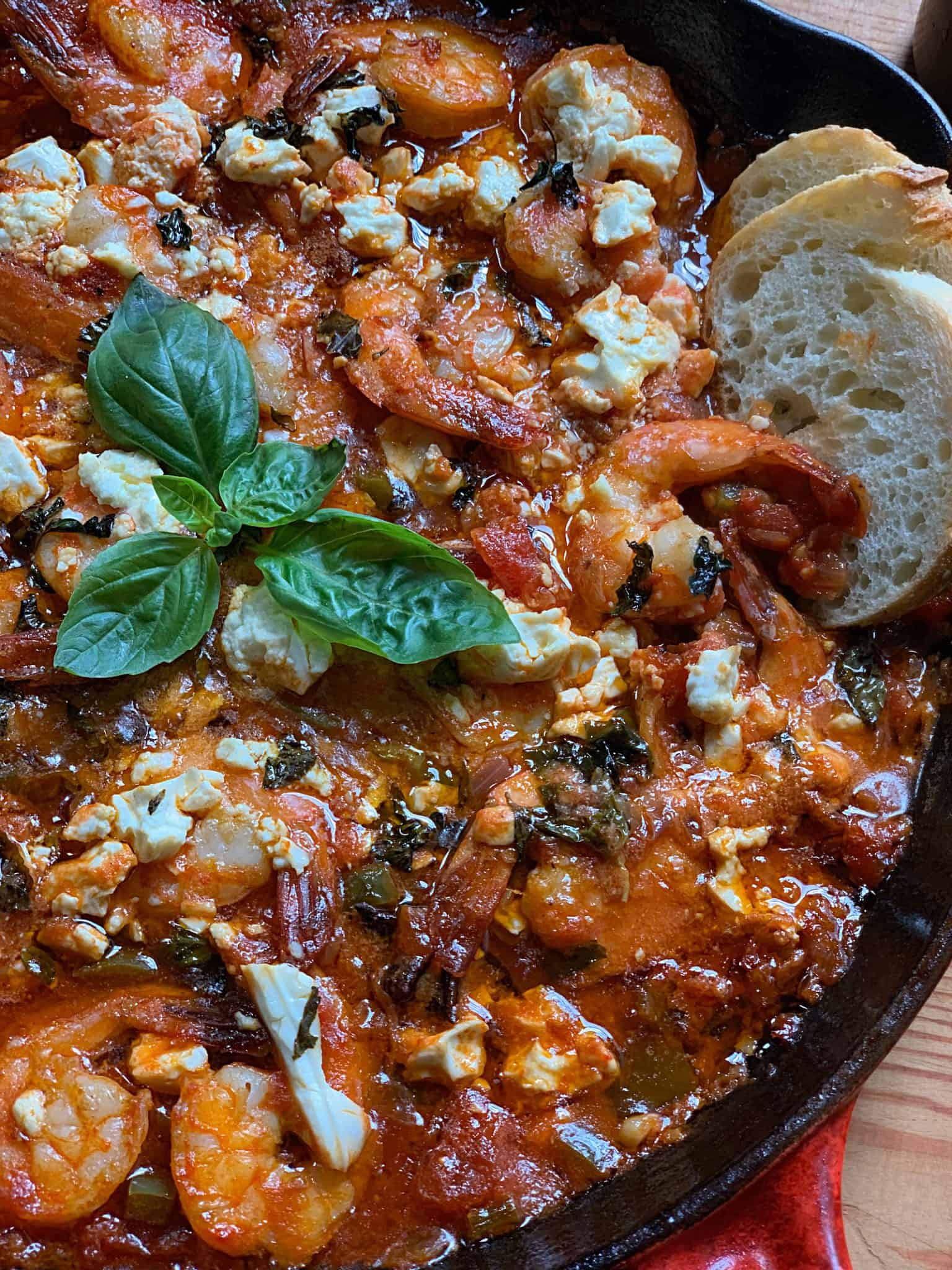 A red cast iron pan filled with a Greek shrimp bake - garides saganaki. It has simple fresh ingredients like juicy tomatoes, tender shrimp, onions, peppers and a secret weapon, a shot of ouzo! Some basil, star anise and red cili flakes are on the side.
