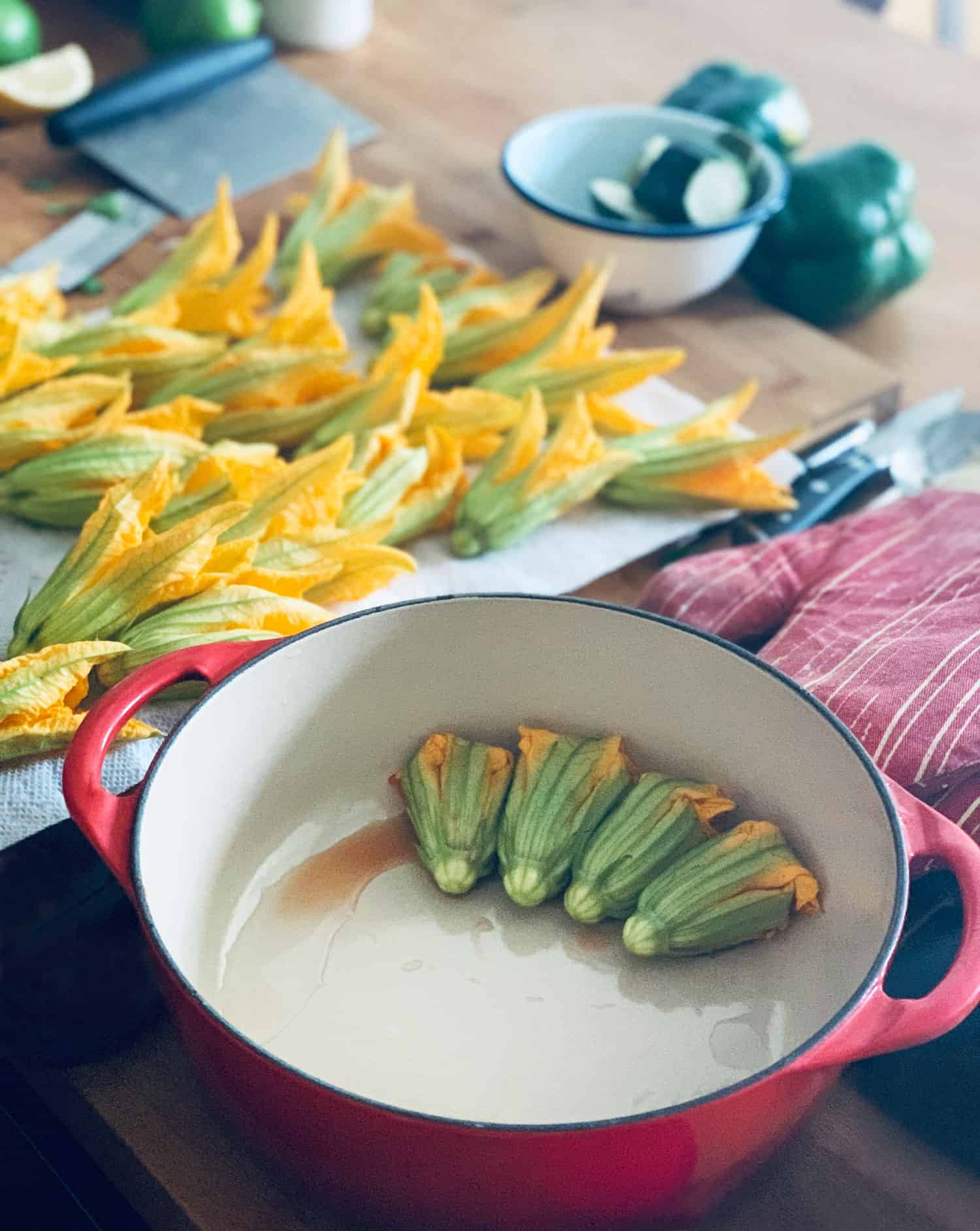 Stuffed squash blossoms in a red pot, in the background blossoms freshly washed on a paper towel and some cut up vegetables in a bowl.