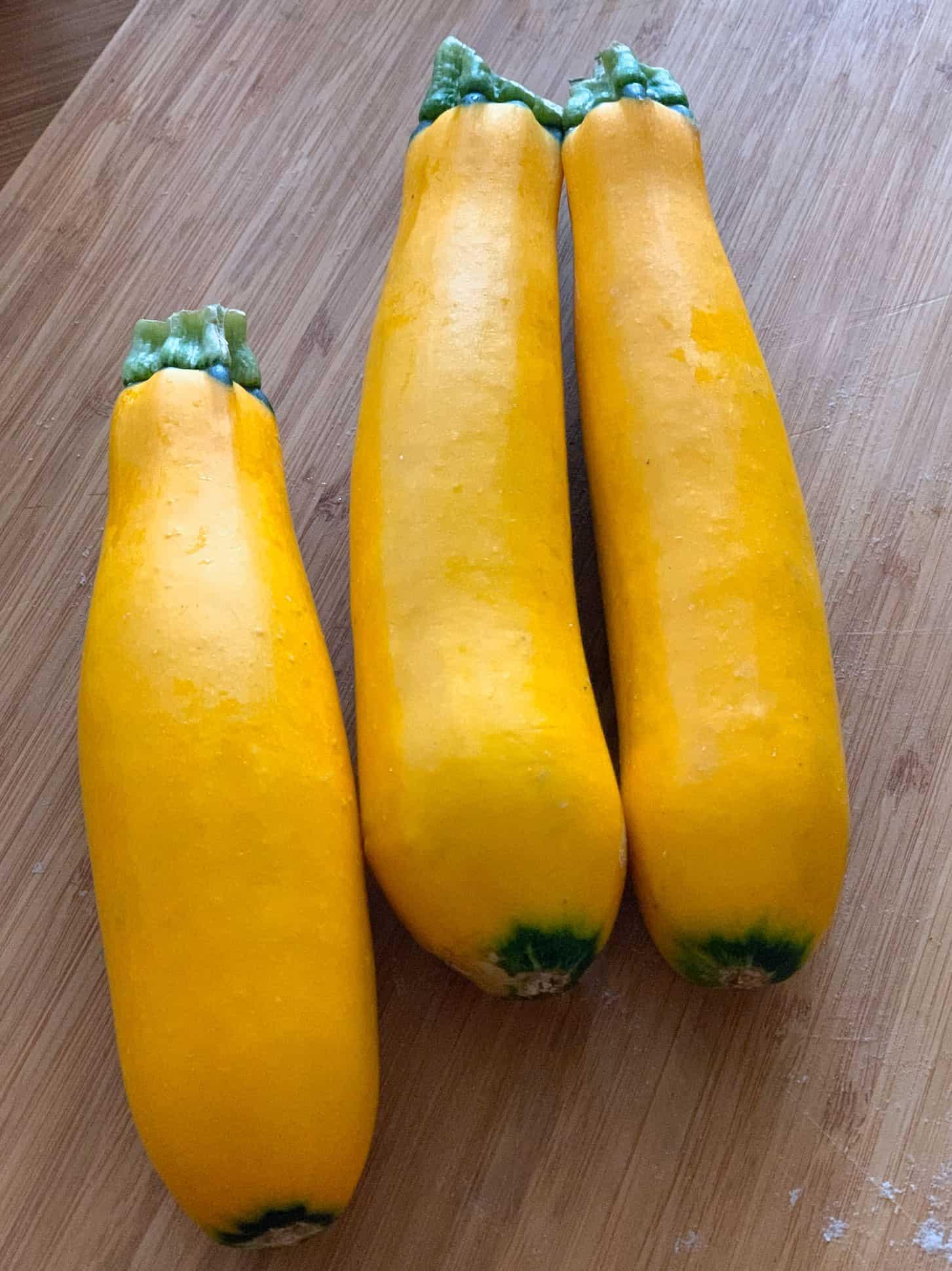 three yellow squash zucchini