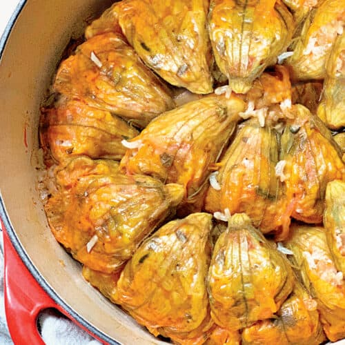 A red pot filled with stuffed zucchini flowers