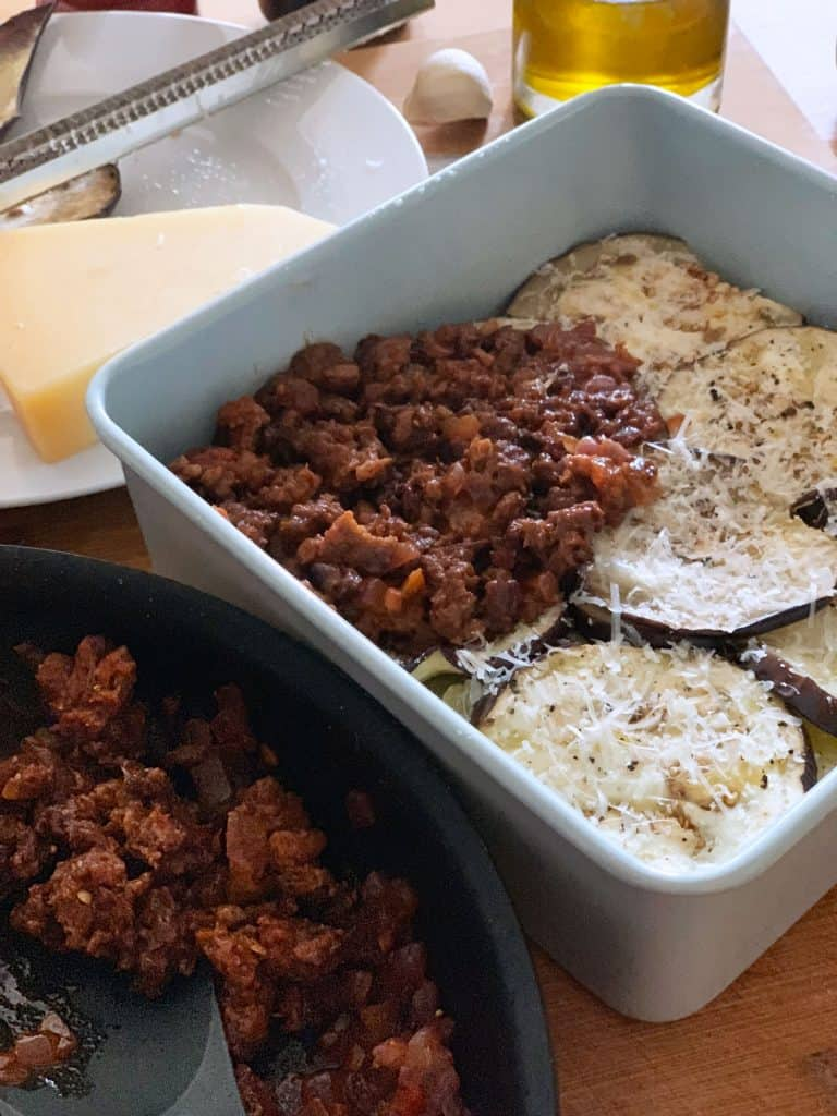 Greek vegetarian moussaka being assembled. A pan filled with potato and eggplant slices topped with plant based meat sauce.