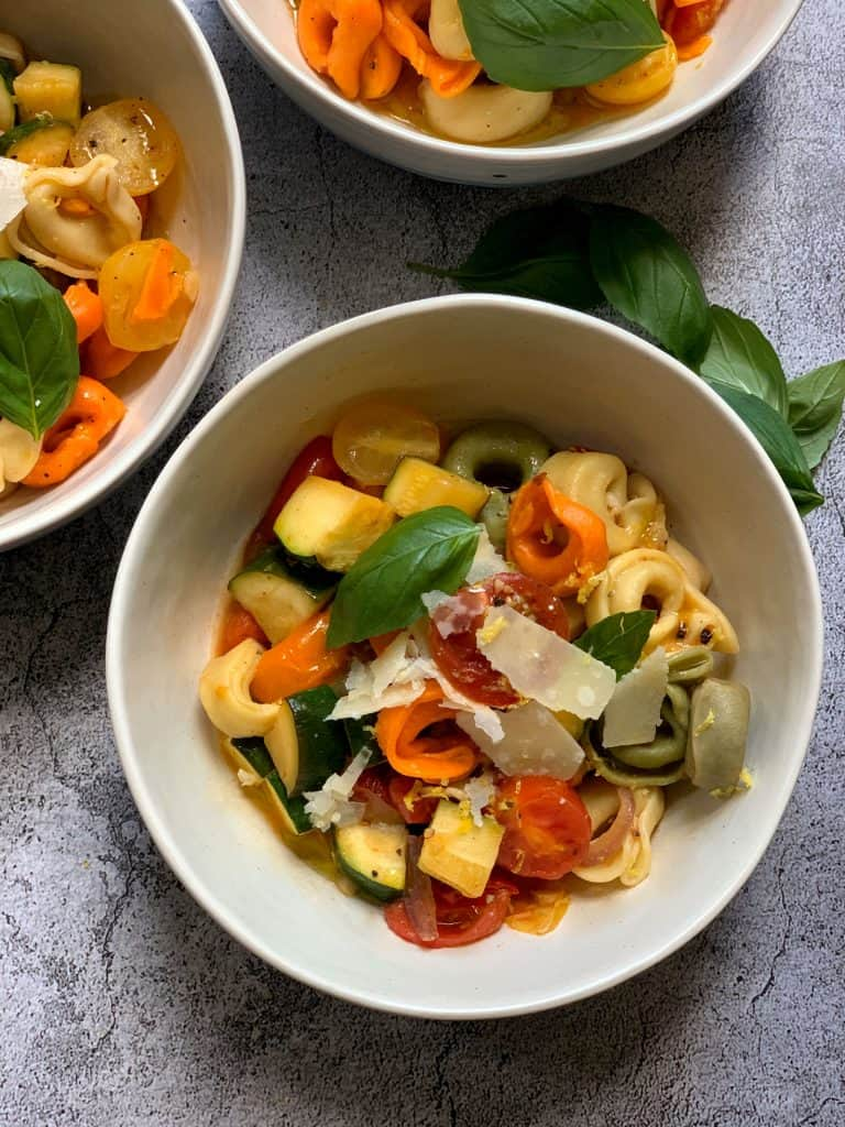 A white plate with colorful tortellini pasta with zucchini, tomatoes and shaved parmesan cheese.