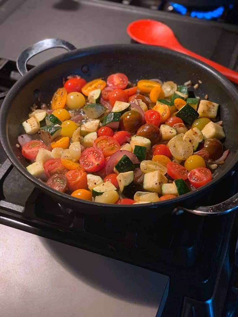 A frying pan cooking zucchini, tomatoes with garlic and olive oil.