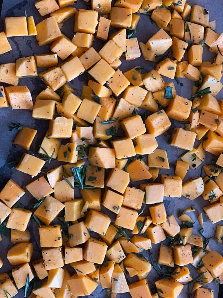 A baking sheet with cubes of butternut squash, dressed in olive oil, slat and pepper and fresh sage leaves