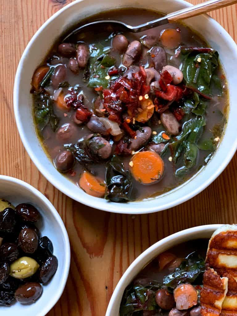 Close up of 3 bowls with heirloom bean soup with aromatic winter greens, fresh herbs and veggies. A piece of grilled halloumi cheese is on the side and a bowl with olives.