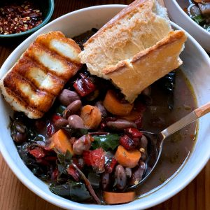 A bowl with heirloom bean soup with aromatic winter greens, fresh herbs and veggies. A piece of grilled halloumi cheese is on the side and a piece of crusty bread.
