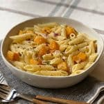 A bowl with penne pasta with cubes of butternut squash, sage and parmesan cheese and olive oil. A spoon and a fork, a napkin, everything is on a tablecloth.