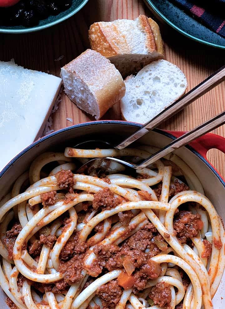 A pot full of beef ragu pasta a piece of romano cheese and a couple of pieces of bread.
