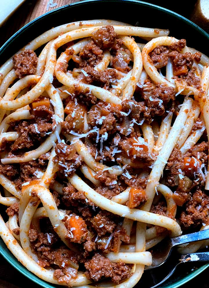 A bowl of beef ragu pasta, on the left a piece of romano cheese, above the bowl is a dish with tomatoes and olives and a couple of pieces of bread.