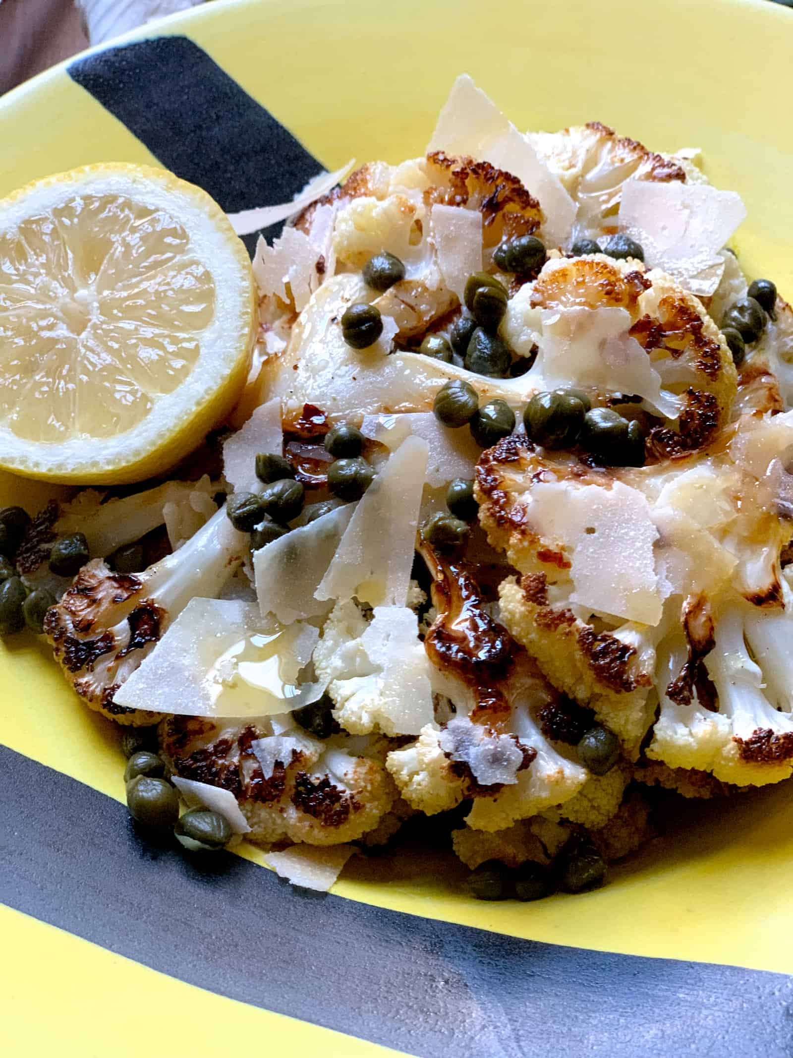 A yellow and black plate with roasted cauliflower, capers, shaved parmesan cheese and olive/lemon dressing. Half a lemon is on the side of the plate.