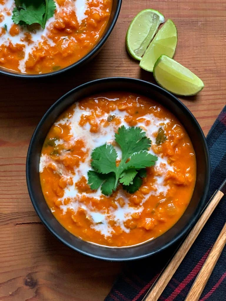 A bowl with curried red lentil, tomato & coconut soup.