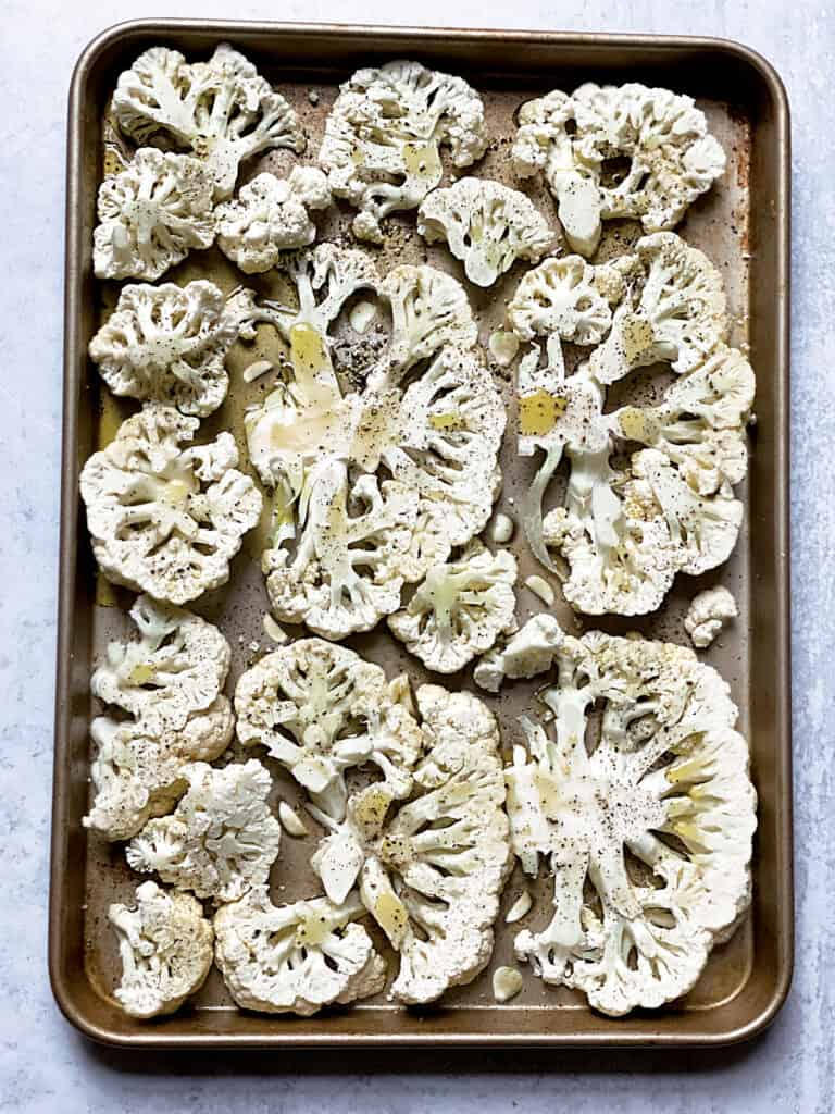 A baking sheet with cauliflower steaks, garlic and olive oil.