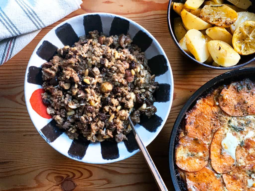 A serving bowl with traditional Greek turkey stuffing with chestnuts, dates and pine nuts. Above is a bowl with lemon roasted potatoes and a pan with sweet potato au gratin.