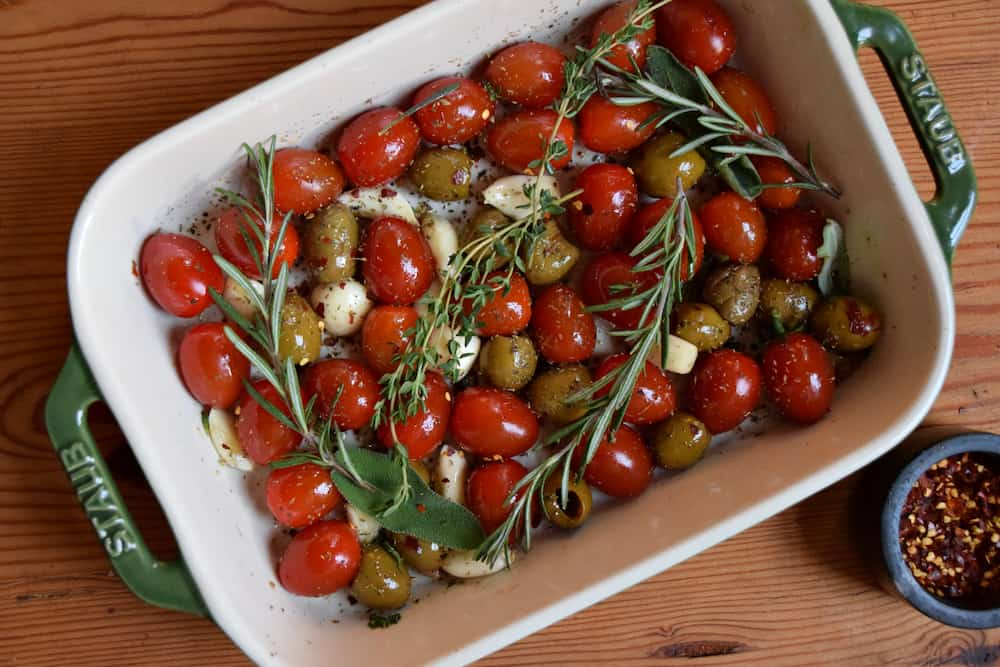 A green baking dish with fresh cherry tomatoes, olives, garlic cloves, olive oil and lots fresh herbs.