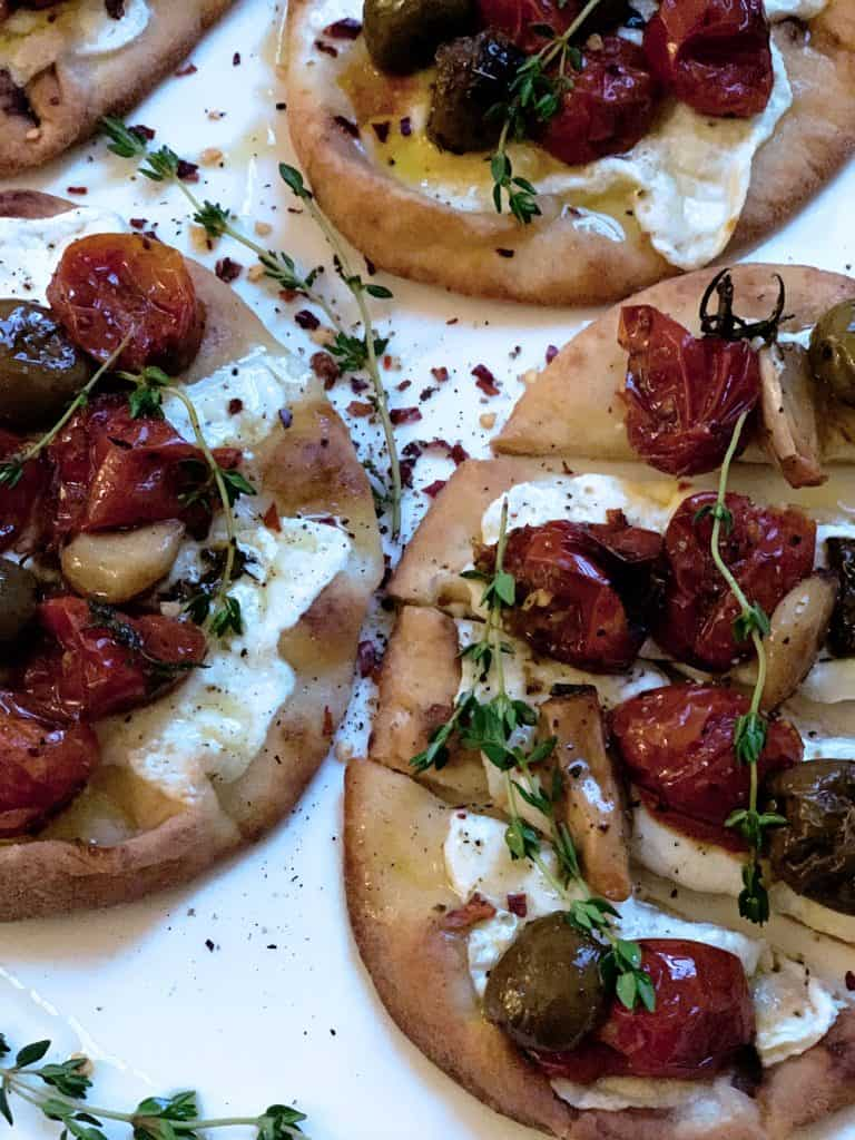 Pita bread with melted mozzarella and on top are baked tomatoes garlic and olives with sprigs of fresh herbs.