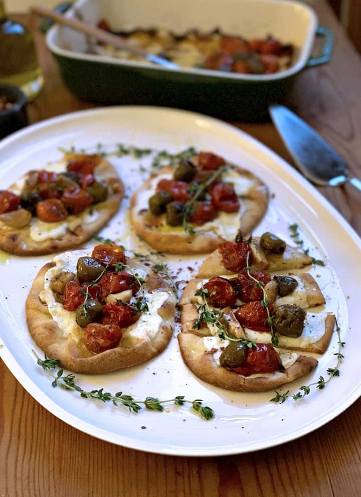A platter with 4 pita breads with melted mozzarella and on top are baked tomatoes garlic and olives with sprigs of fresh herbs.