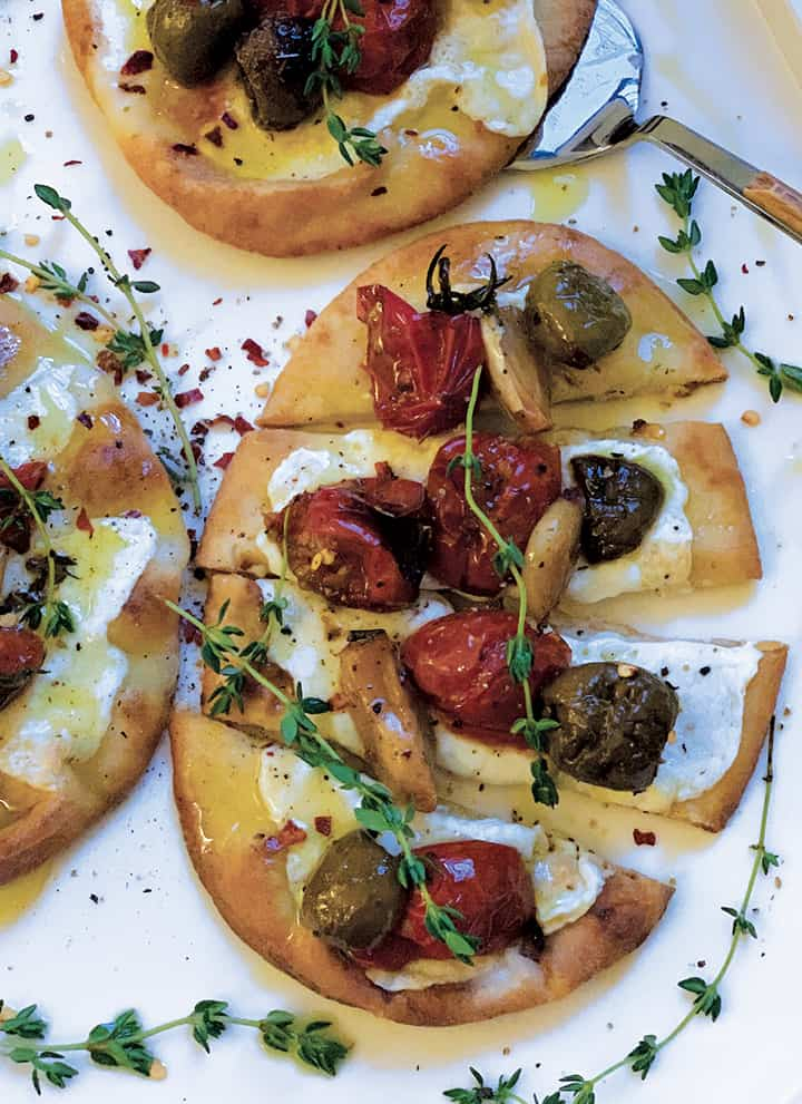 Feature image: A pita bread with melted mozzarella and on top are baked tomatoes garlic and olives with sprigs of fresh herbs.