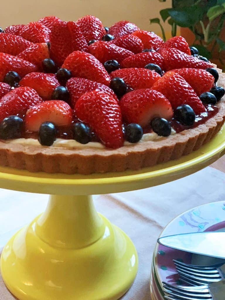 A yellow cake stand containing a berry tart with strawberries and blueberries.
