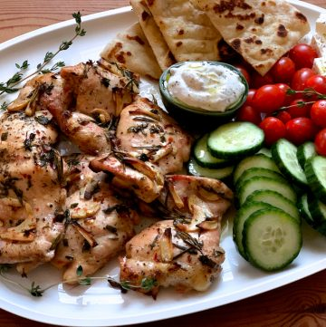 A white platter with fresh herbs, roasted chicken thighs, a small bowl with tzatziki dip, cherry tomatoes, lots of cucumber slices, feta cheese cubes and cut up pita.