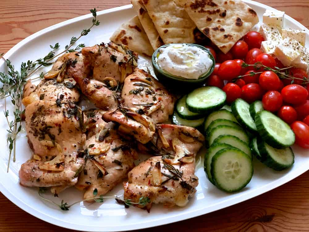 A white platter with fresh herbs, roasted Greek herb chicken thighs, a small bowl with tzatziki dip, cherry tomatoes, lots of cucumber slices, feta cheese cubes and cut up pita.