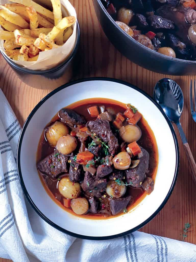 A plate with Greek Red Wine Beef Stew and french fries.