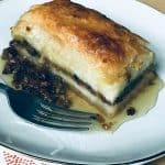 A plate with a baklava piece, syrup and nuts and a fork.