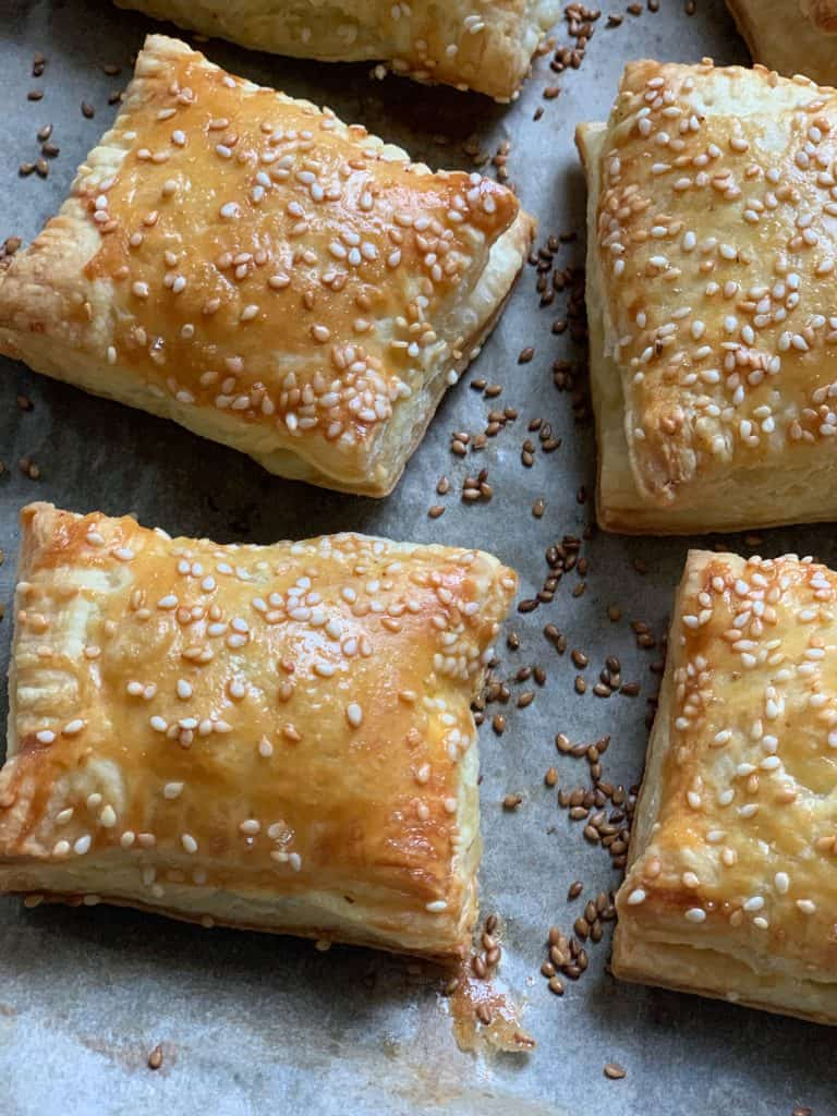 Cheese puff pastries on parchment paper.