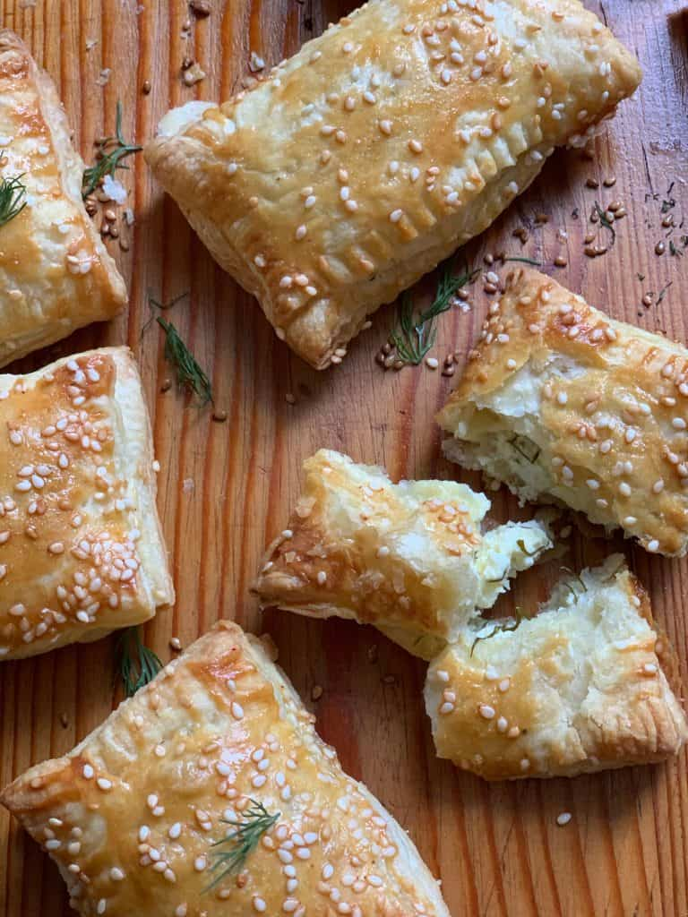 Cheese puff pastries on wood with scattered dull all round.