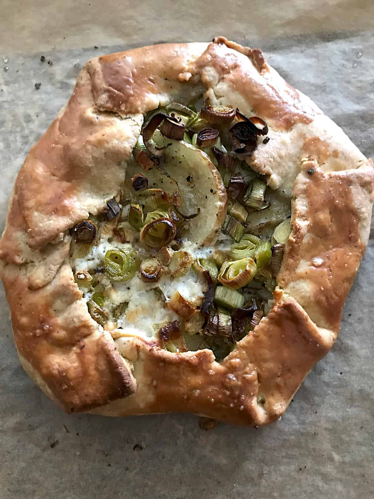 A leek and potato galette on parchment paper.