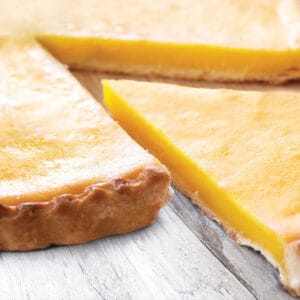 A Meyer lemon ginger tart with a piece cut out on white wood.