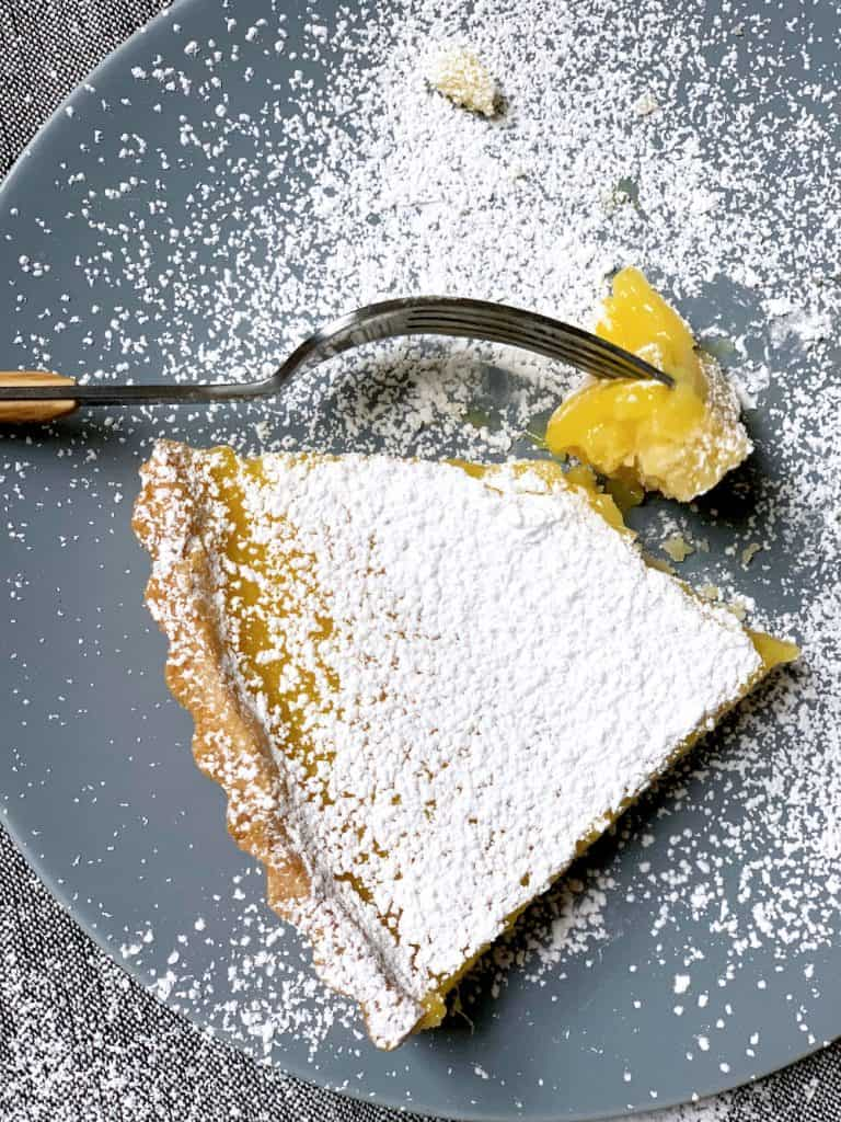 A lemon ginger tart piece on plate with a fork and little tart piece.