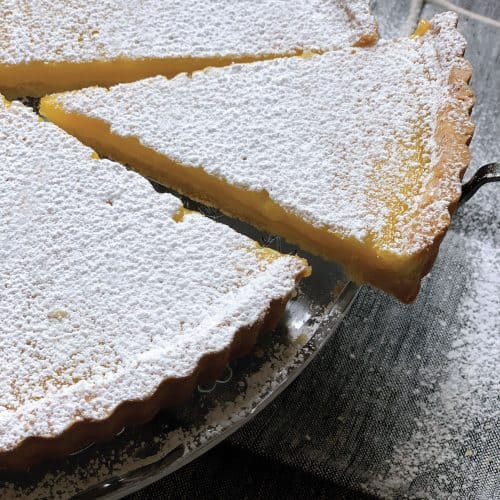 A lemon ginger tart with a piece cut out.