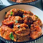 plate with cumin meatballs in red sauce-greek soutzoukakia and another plate in the background.