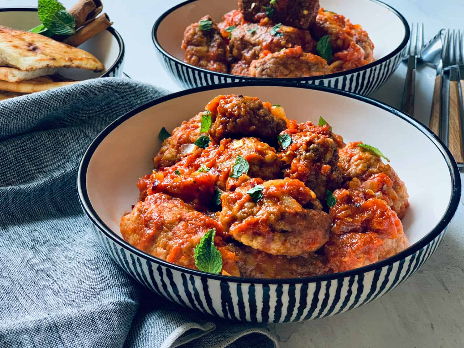 Two plates with cumin meatballs in red sauce-greek soutzoukakia and another plate in the back with cut up pita breads.
