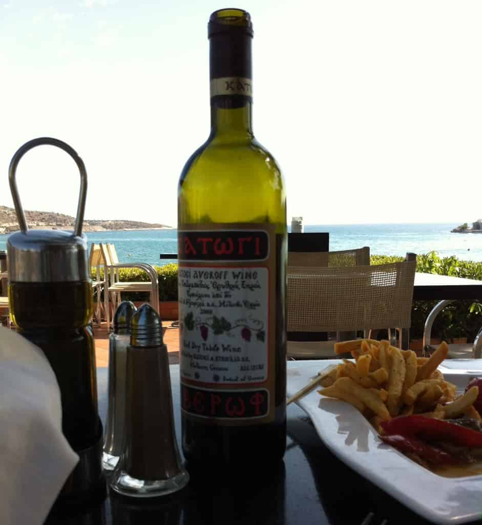 A bottle of wine, a plate with calamari, utensils on a table outdoors in Vouliagmeni, Athens, Greece.